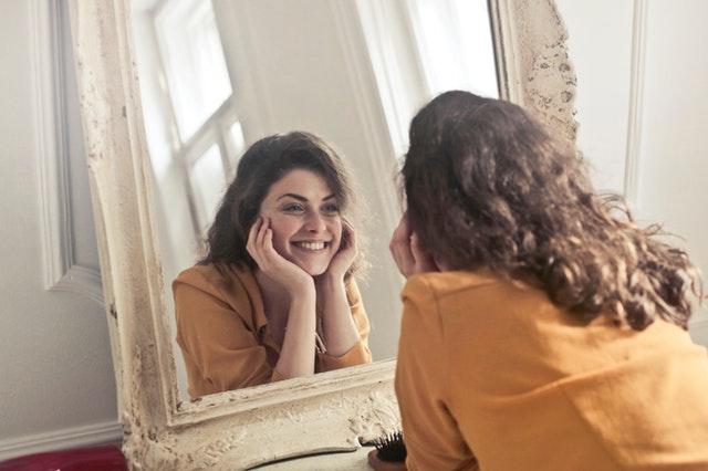 Usmiata žena pozerajúca sa do zrkadla