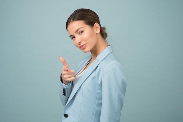 Žena v modrom saku, ktorá ukazuje prstom