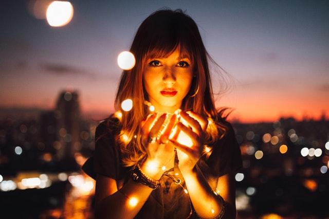 Žena, ktorá v rukách drží reťaz zo svetielok