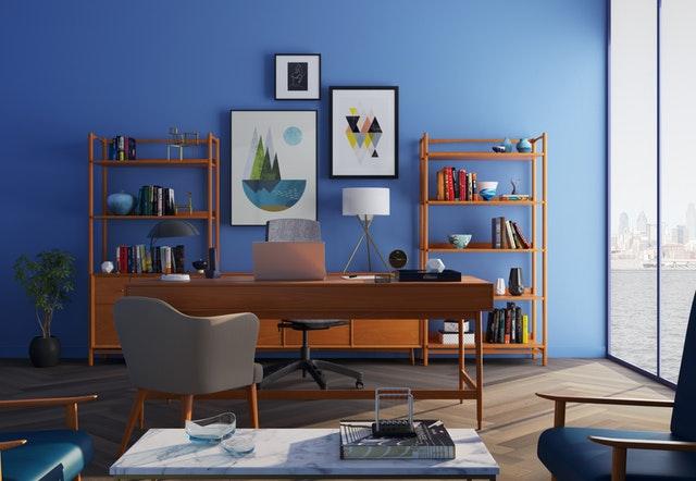 Pracovňa s modrou stenou a veľkými sklenenými dverami s výhľadom na more.jpg